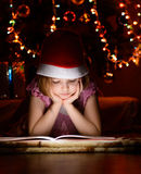 Little girl reading a book beside  Christmas tree Stock Image