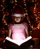 Little girl reading a book beside  Christmas tree Royalty Free Stock Photo