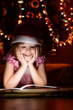 Little girl reading a book beside  Christmas tree Stock Photo