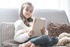 Little girl reading a book on a comfortable sofa, beautiful emotions stock photography
