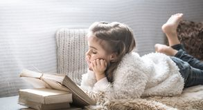 Little girl reading a book on a comfortable sofa, beautiful emotions royalty free stock photo