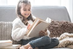 Little girl reading a book on a comfortable sofa, beautiful emotions stock photos