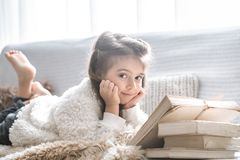 Little girl reading a book on a comfortable sofa, beautiful emotions stock photo