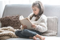 Little girl reading a book on a comfortable sofa, beautiful emotions royalty free stock photography