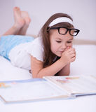 Little girl is reading a book. Cute little girl is reading a book Stock Photo
