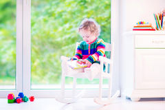 Little girl reading a book. Cute curly little girl, funny toddler wearing a warm colorful knitted dress reading a book relaxing in a white rocking chair next to Royalty Free Stock Photo