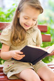 Little girl is reading a book Stock Image