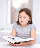 Little girl is reading a book. Cute little girl is reading book while sitting at table, indoor shoot Royalty Free Stock Images