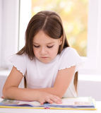 Little girl is reading a book. Cute little girl is reading book while sitting at table, indoor shoot Royalty Free Stock Photos