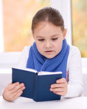 Little girl is reading a book. Cute little girl is reading book while sitting at table, indoor shoot Stock Photo