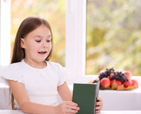 Little girl is reading a book. Cute little girl is reading book while sitting at table, indoor shoot Stock Photos