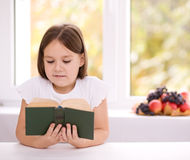 Little girl is reading a book. Cute little girl is reading book while sitting at table, indoor shoot Royalty Free Stock Photography