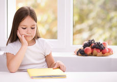 Little girl is reading a book. Cute little girl is reading book while sitting at table, indoor shoot Stock Image