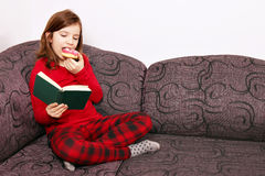 Little girl reading a book and eating donut Stock Images