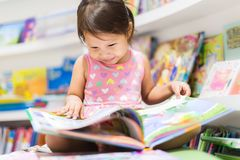 Little girl reading a book. Education stock image