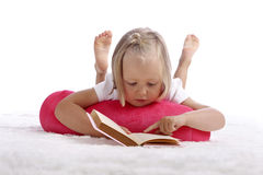 Little girl reading a book on the floor Royalty Free Stock Photo