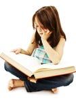 A little girl reading a book on the floor Stock Photos