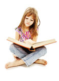A little girl reading a book on the floor Stock Photo