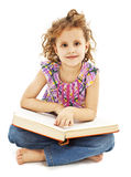 A little girl reading a book on the floor Royalty Free Stock Images