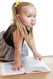 Little girl reading a book on the floor Stock Image
