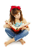 A little girl reading a book on the floor Royalty Free Stock Photography