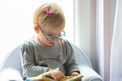 Little girl reading book. At home Royalty Free Stock Photos