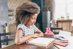 Little girl reading book. Little girl reading a book at the kitchen table Royalty Free Stock Photos