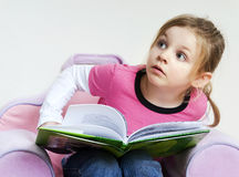 Little girl reading a book and looking up Stock Photos