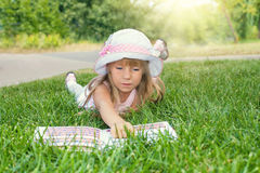 Little girl reading a book. Lying on the grass in the park stock images