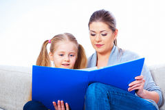 Little girl reading book with mother. Stock Image