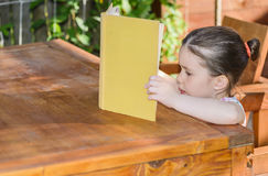 Little girl reading a book outdoor Stock Photo