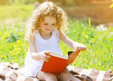 Little girl reading a book. Outdoors Stock Photography