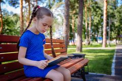 Cute little girl is reading a book outdoors royalty free stock photo