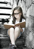 Little girl is reading a book outdoors Stock Photo