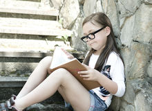 Little girl is reading a book outdoors Royalty Free Stock Photos