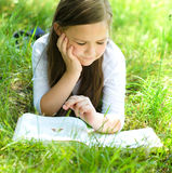 Little girl is reading a book outdoors Royalty Free Stock Image
