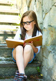 Little girl is reading a book outdoors Royalty Free Stock Images