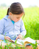 Little girl is reading a book outdoors Stock Image