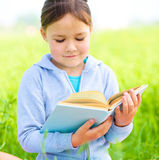 Little girl is reading a book outdoors Stock Images