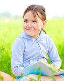 Little girl is reading a book outdoors Royalty Free Stock Photo