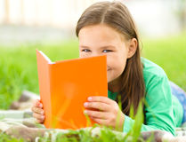 Little girl is reading a book outdoors Stock Photos