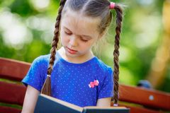 Little girl reading a book in the outdoors. royalty free stock photos