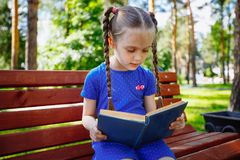 Little girl reading a book in the outdoors. stock images