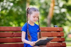 Little girl reading a book outdoors. stock photos