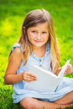 Little girl reading book outside Stock Images