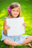 Little girl reading book outside. Cute little girl reading book outside on grass in backyard flower in the ear Stock Image