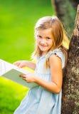 Little girl reading book outside. Cute little girl reading book outside on grass in backyard mischievous look Stock Photo