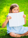 Little girl reading book outside Stock Photo
