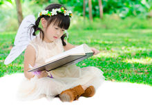 Little girl reading book in the park Stock Image
