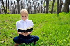 Little girl reading book in the  park. Little blond girl reading book between green spikes meadow garden Royalty Free Stock Photos